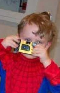 Aidan plays with a camera, while the photograph captures a white glow in his eye.