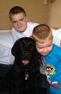 Kieran and Cameron with a black labrador-retriever dog