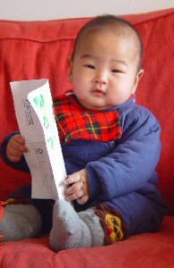 Baby Lele sits on a big red sofa, holding some papers as if ready to read deeply.
