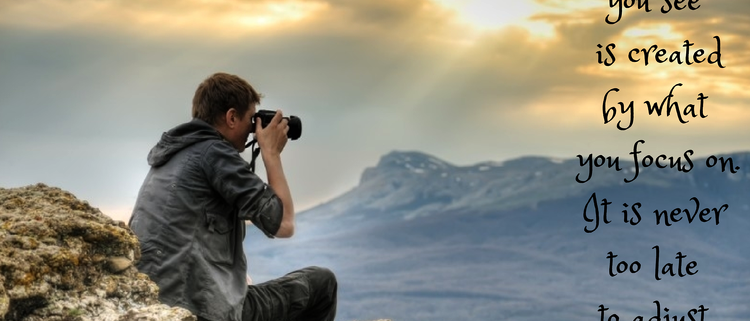 """Quote set alongside an image of a photographer adjusting the camera for the perfect shot of a view from on top of a mountain. Quote: """"The world you see is created by what you focus on. It is never to late to adjust your lens."""""""