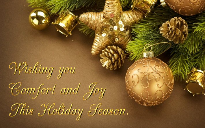 A seasonal greeting framed with gold bells, gilded baubles, gold fircones and lush foliage. The message reads: wishing you comfort and joy this holiday season.