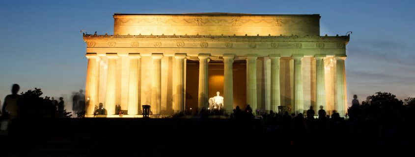 The Lincoln Memorial, lit up in gold against a deep blue sky.