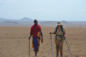Abby walks across a vast desert plain, alongside a Massai warrior. Abby is wearing neutral coloured trekking gear and sunhat, carrying a backpack with a drinking tube visible attached to one strap, and holding walking poles. Her companion is wearing wraps of blue, black, red and gold checkered and striped cloth, and various bead ornaments, and carries a walking pole.
