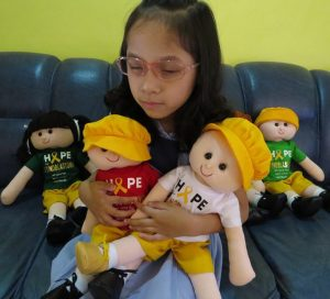 A young Asian girl wearing glasses and a shy smile sits on a blue couch against a pale green background. Her face is turned slightly down and away from the camera. She holds several cloth dolls weating hats and t-shirts bearing the words