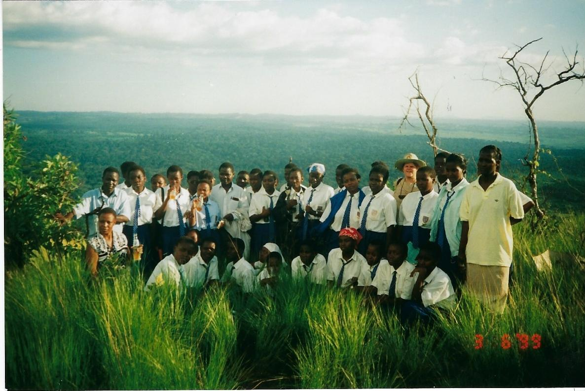 Abby poses with a group of African schoolgirls and their teachers at the top of a hill overlooking a forest.