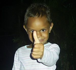 A young Pacific Islander girl shares a thumbs up gesture, her outstretched arm slightly obscuring a shy smile. A white glow is visitle in one eye. Her white outfit glows from against the dark background.