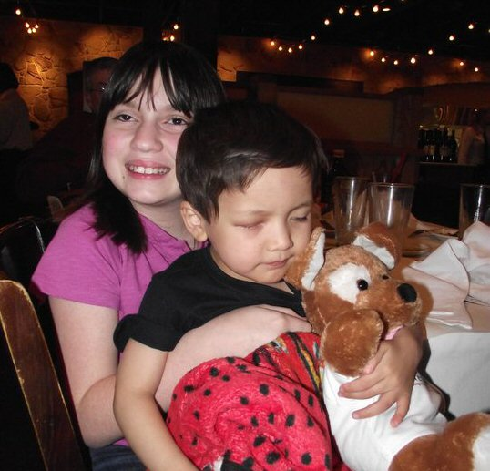 Photo of two young children diagnosed with retinoblastoma. An older girl hugs a younger boy who sits with his back against her chest, holding a teddy bear. The girl has a broad smile and her face is turned slightly away from the camera. The boy's eyes are closed and he has an expression of deep thought.