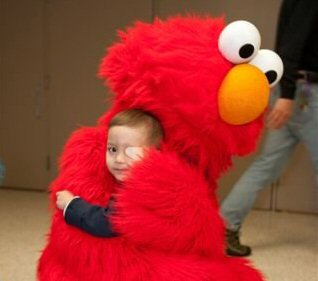 A young boy is wrapped up in a hug from an Elmo character.