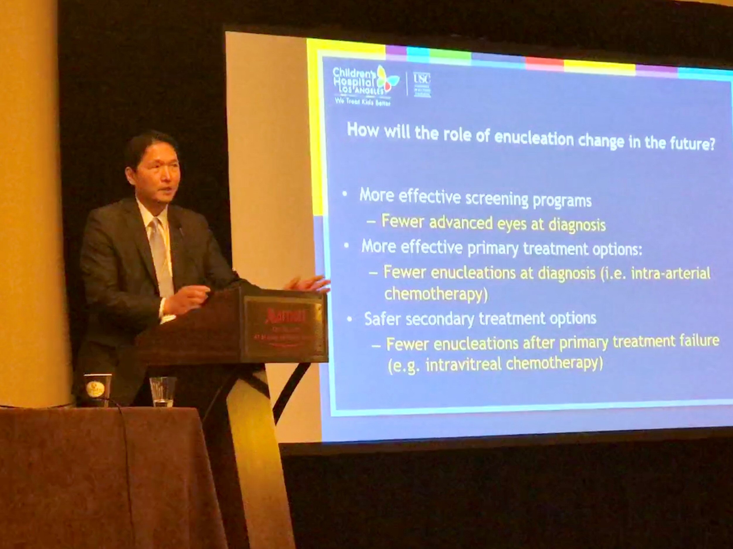 "Jonathan Kim presents on the changing role of enucleation, and its continued importance as life-saving treatment for retinoblastoma. The slide seen behind him is titled: ""how will the role of enucleation change in the future? Three evolving scenarios are followed by their impacts: More effective screening programs – fewer advanced eyes at diagnosis; More effective primary treatment options, i.e. intra-arterial chemotherapy (fewer enucleations at diagnosis); Safer secondary treatment options, i.e. intravitreal chemotherapy (fewer enucleations after primary treatment)."