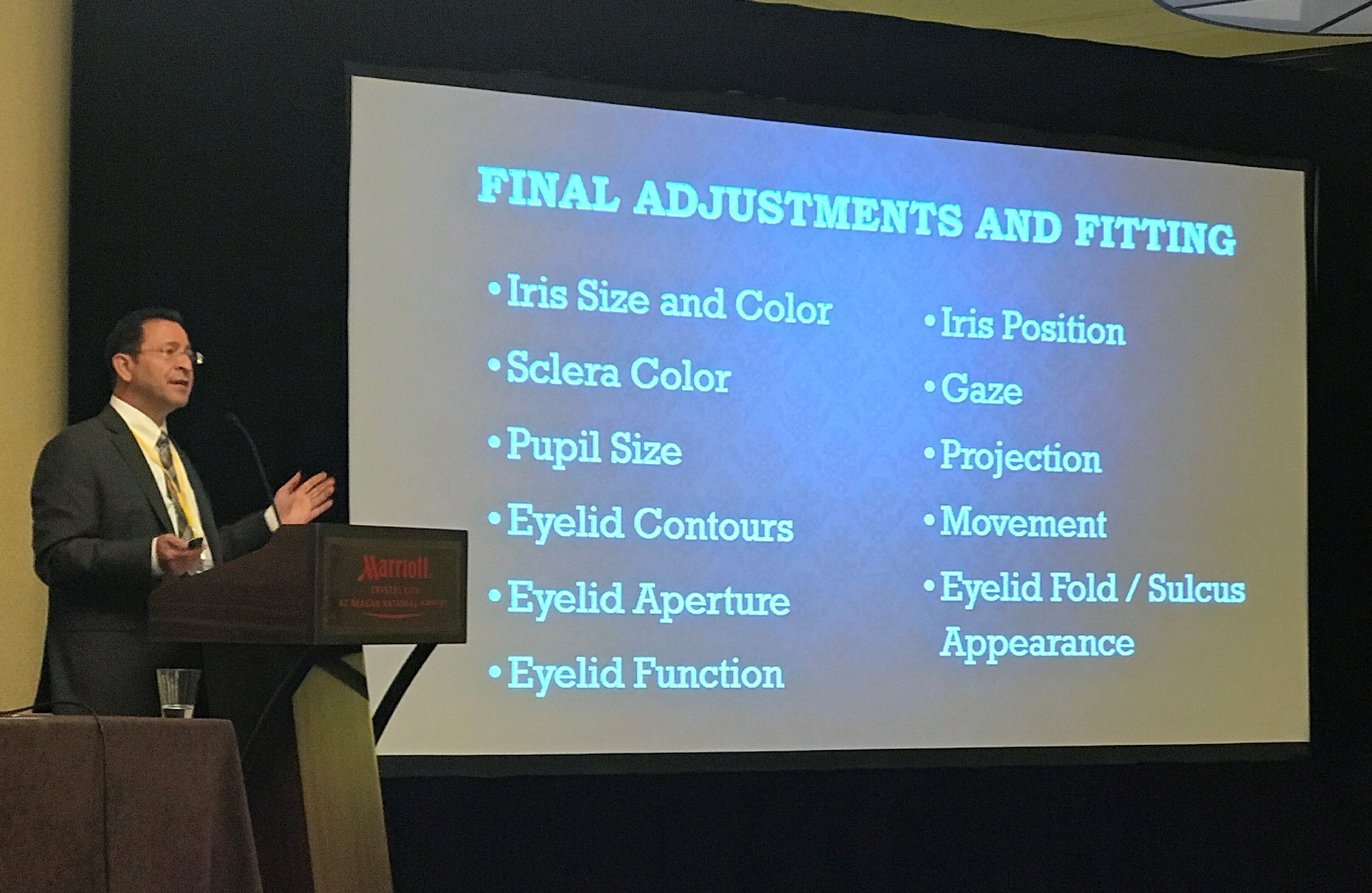 "Stephen Haddad describes the process of fitting an artificial eye. The slide seen behind him is titled ""Final Adjustment and Fitting"" and lists the different elements of the process: iris size and color, sclera color, pupil size, eyelid contours, eyelid aperture, eyelid function, iris position, gaze, projection, movement, and eyelid fold / sulcus appearance."