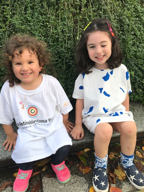 Two children sit together, one wearing a One Rb World t-shirt.