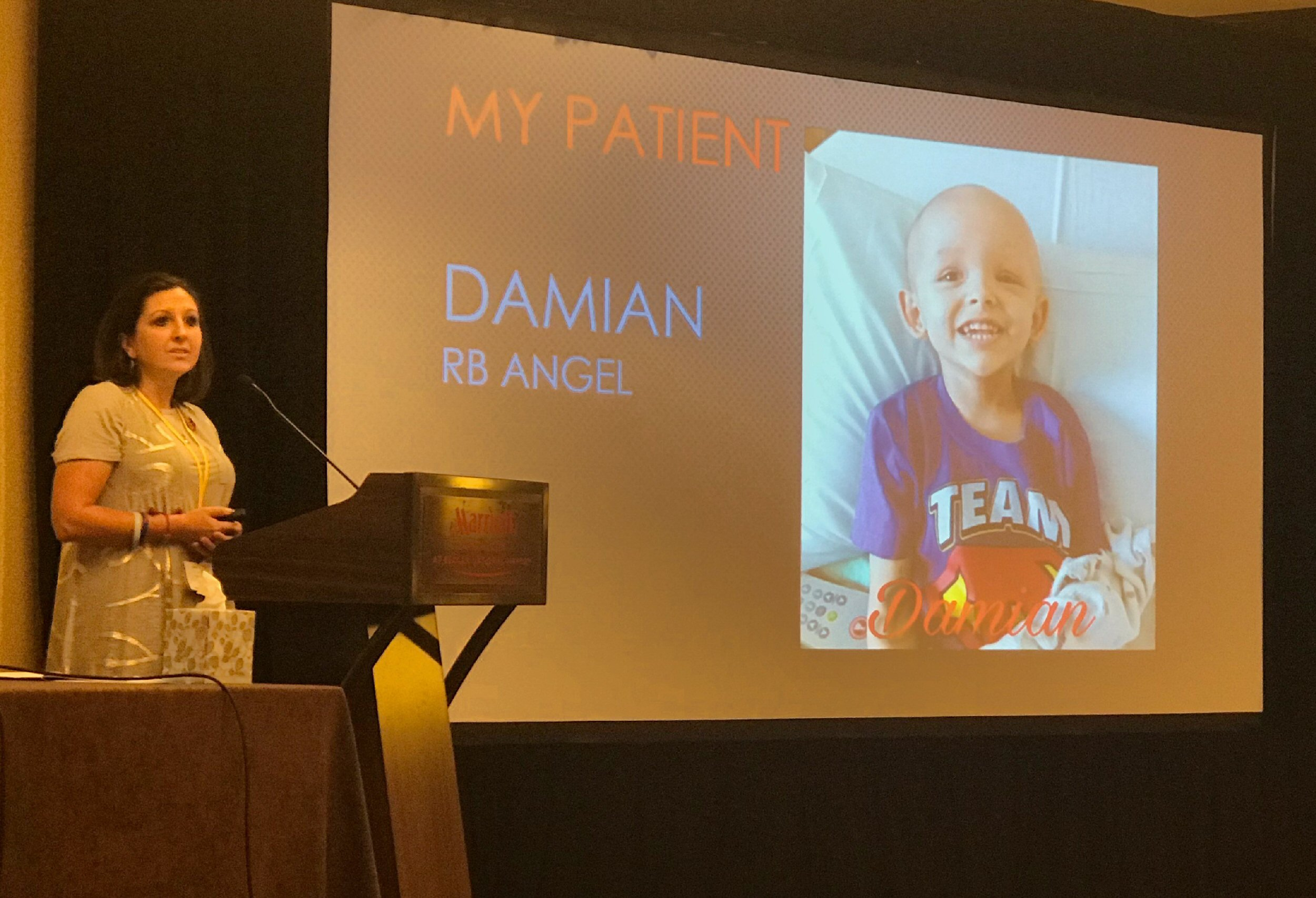 "Sarah Hancock highlighted the importance of parent intuition. The slide behind her is titled ""My Patient"" and shows a photo of her son, Damian, with the words, ""Damian, RB Angel""."