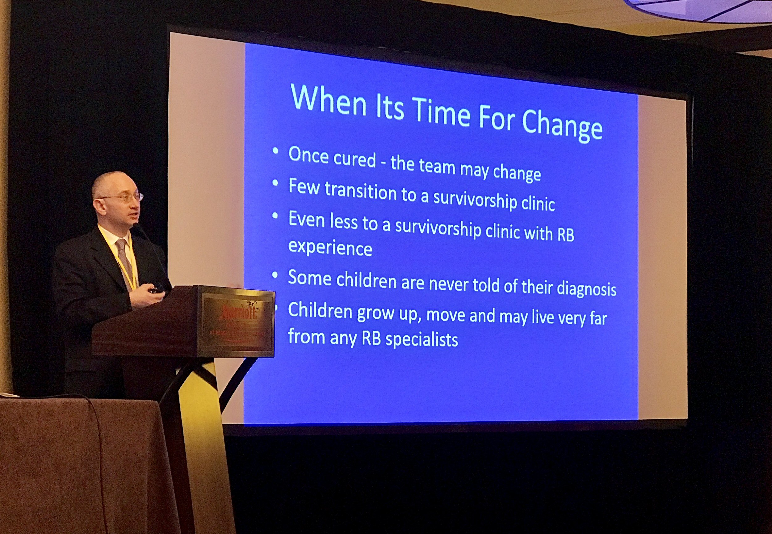 "Dan Gombos presents on the challenges of obtaining effective care for the adult with distant history of Rb. The slide behind him is titled ""When It's Time For Change"" and reads: Once cured – the team may change; Few transition to a survivorship clinic; Even less to a survivorship clinic with Rb experience; Some children are never told of their diagnosis; Children grow up, move, and may live very far from any Rb specialists."