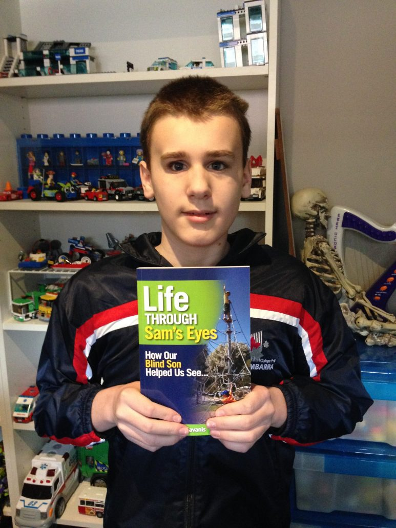 "Sam holds the published book, ""Life Through Sam's Eyes""."