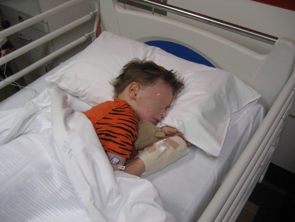 Ih his hospital bed, Sam recovers from eye removal surgery. His eye is bandaged and an IV is secured in his hand.