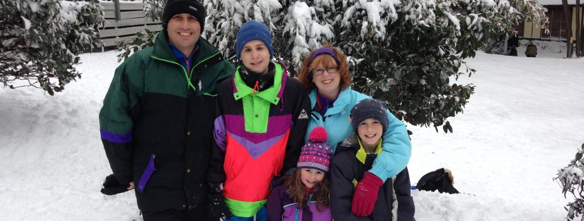 Wrapped up against the cold, Jim and Liza Valavanis and their three children are pictured together in a snowy winter wonderland.