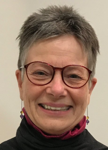 Brenda Gallie, smiling, wearing spectacles.