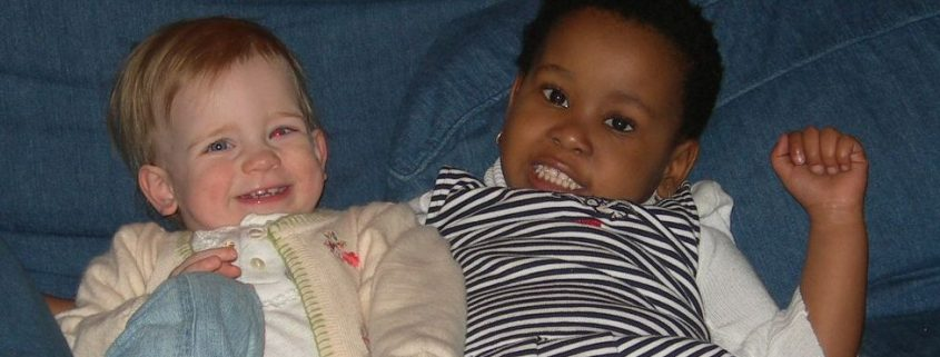 Two young girls, one Caucasian, one African, recline together on a blue sofa, smiling.