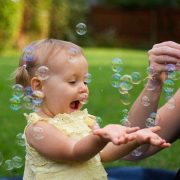 A young girl squeals in delight and holds out her hands, palms up, to catch the bubbles blown by a woman just right of the camera frame.