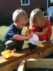A young boy and girl work together in deep concentration to make the perfect mud pie.