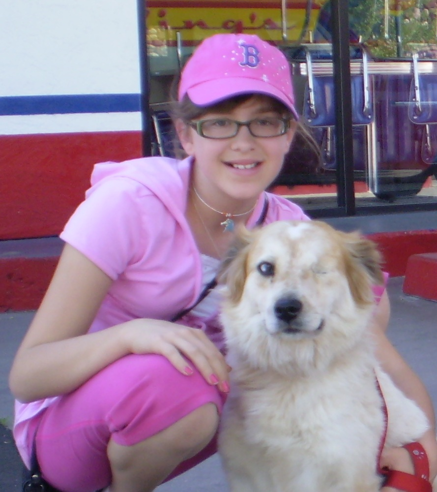 Grace poses with a coffee cream coloured dog who has only one eye. Grace is smiling and wearing glasses, a pink outfit and pink baseball cap.