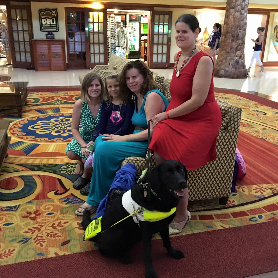The group of friends gather together on a sofa in a hotel lobby, a black lab-retriever guide dog sitting in front.