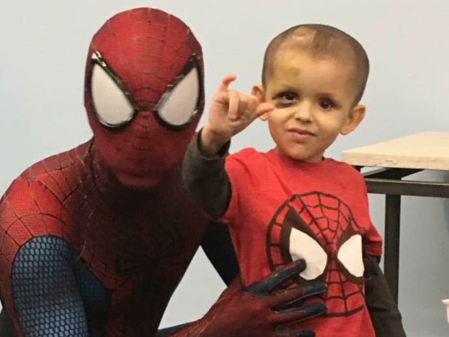 Damian meets his hero, Spiderman, and salutes with Spiderman's hand gesture (extending his thumb, index and little fingers while folding down his middle and ring fingers), which is also the sign language 'ILY' or 'I Love You' sign.