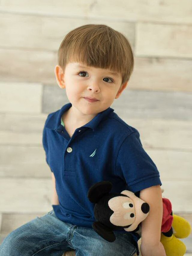 Damian poses, clutching a Mickey Mouse toy to his side.