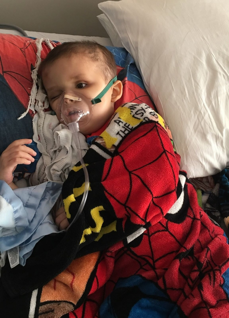 Looking very small against the big pillows that surround him, Small Damian lies wrapped in his Spiderman blanket, an oxygen mask helping him breathe.
