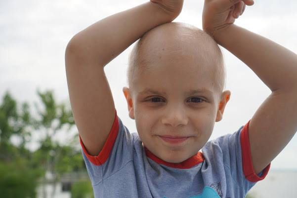 Max is pictured against a backdrop of trees and overcast sky. Bald from chemotherapy, he holds his hands above his head, a small smile on his face.