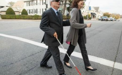 A man wearing dark glasses walks with a woman along a road, guided by his cane and his hand at her elbow.