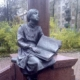 Statue of a blind girl sitting on a plinth, leaning against a post in contemplation while reading a book balanced on her knees and one hand.