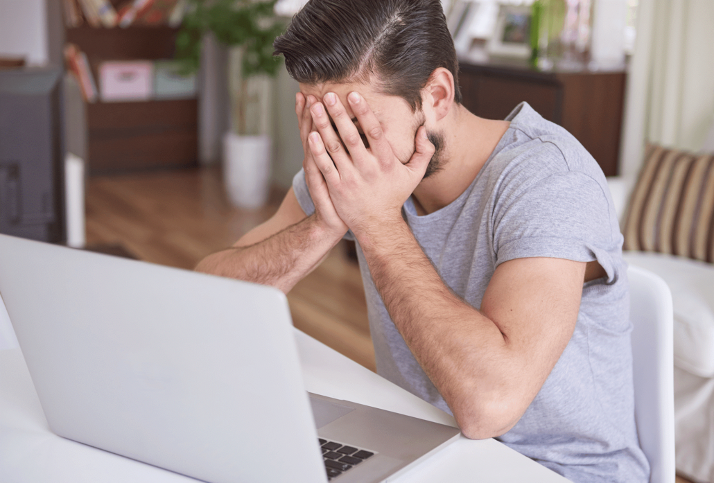A male sits at home in front of his laptop with his head in his hands.