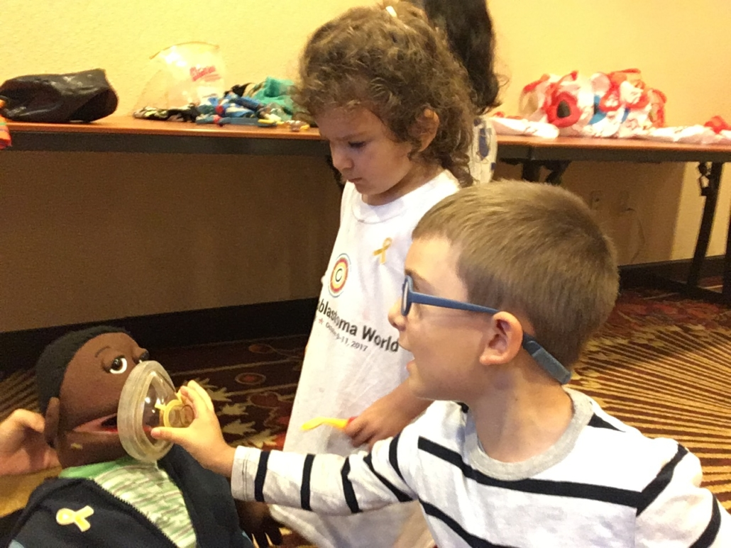 A young boy places a mask over a medical play puppet, while a young girl looks on. The girl is wearing a One Retinoblastoma World t-shirt.