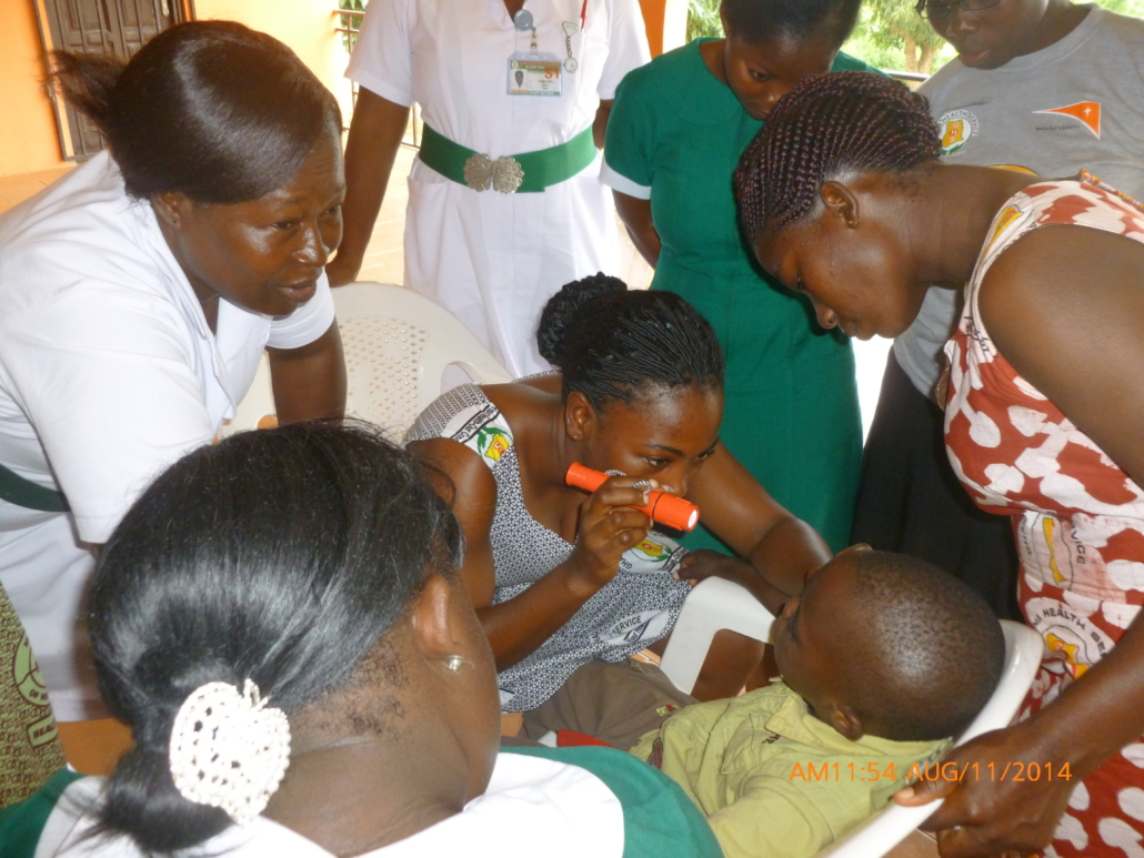 A primary health worker examines a child with a torchlight