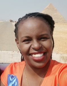 Dr Grace Kariuki smiles broadly, Egypt's pyramids faintly visible in the background.