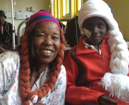 Jayne and a child are pictured wearing long yarn wigs of different colours.