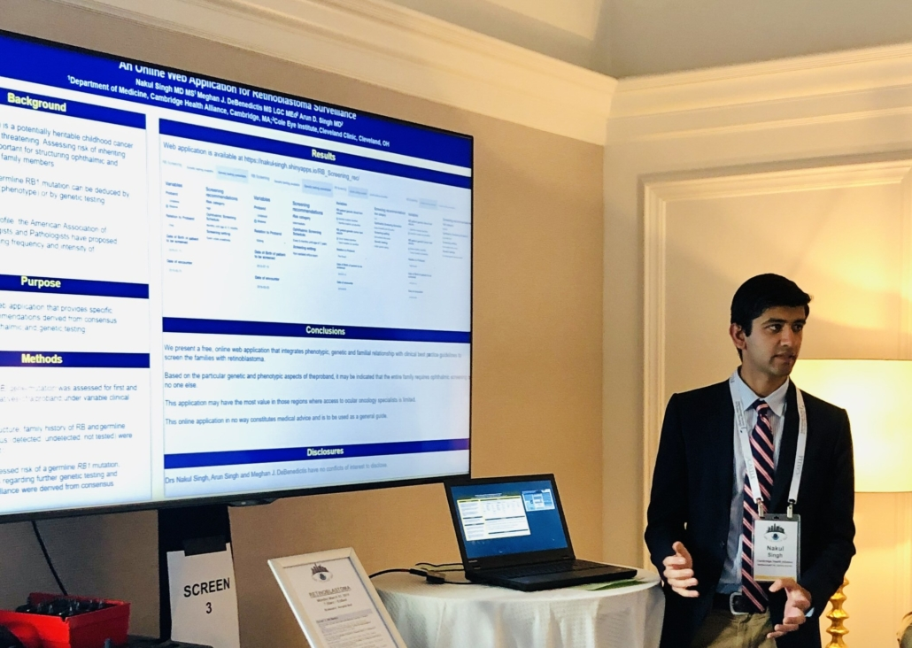 "Dr. Nakul Singh stands next to a laptop computer that projects his poster onto a larger screen. He is looking away from the screens, out to the people in the room – who are off-frame, gesturing with his hands as he talks. The poster's text cannot quite be defined, other than the titles, which are: ""An online web application for retinoblastoma surveillance"". Background / Purpose / Methods / Results / Conclusions / Disclosures."