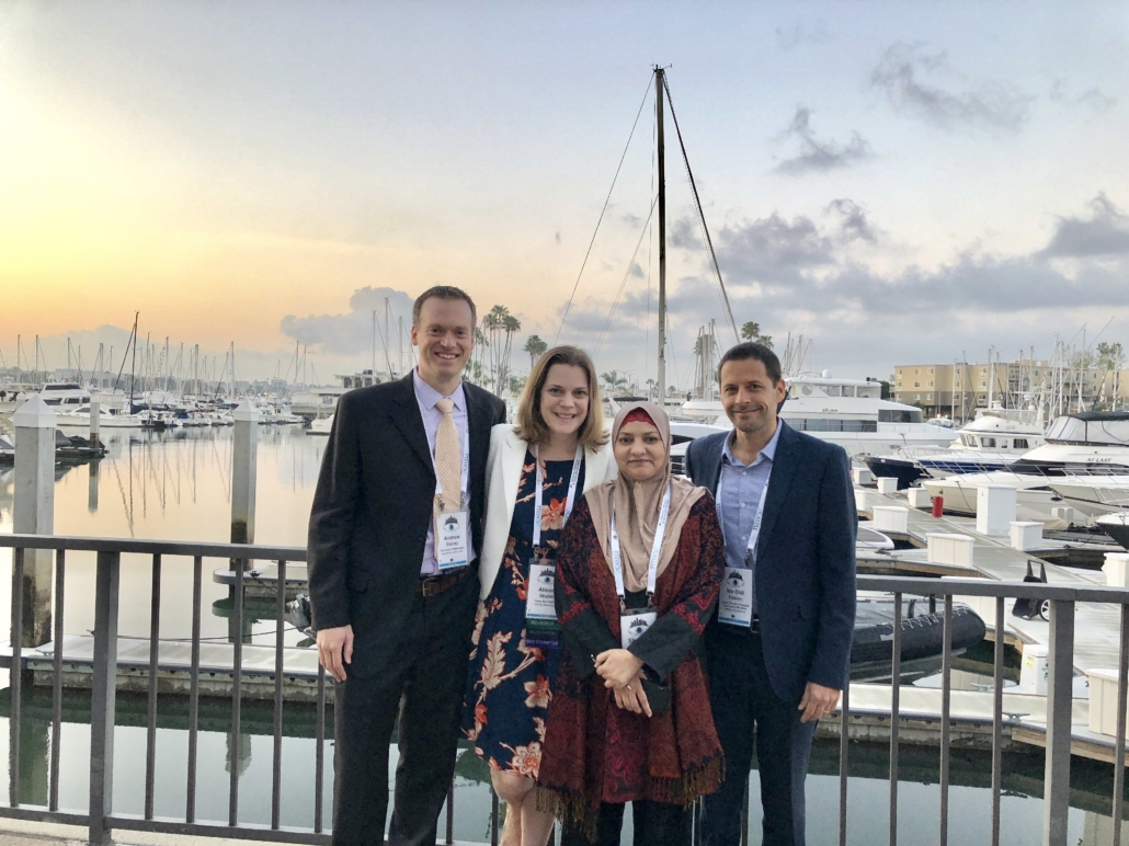 Drs. Andrew Stacey, Alison Skalet, Shabana Chaudry, and Ido Didi Fabian stand together, sun beginning to set over the busy marina behind them.