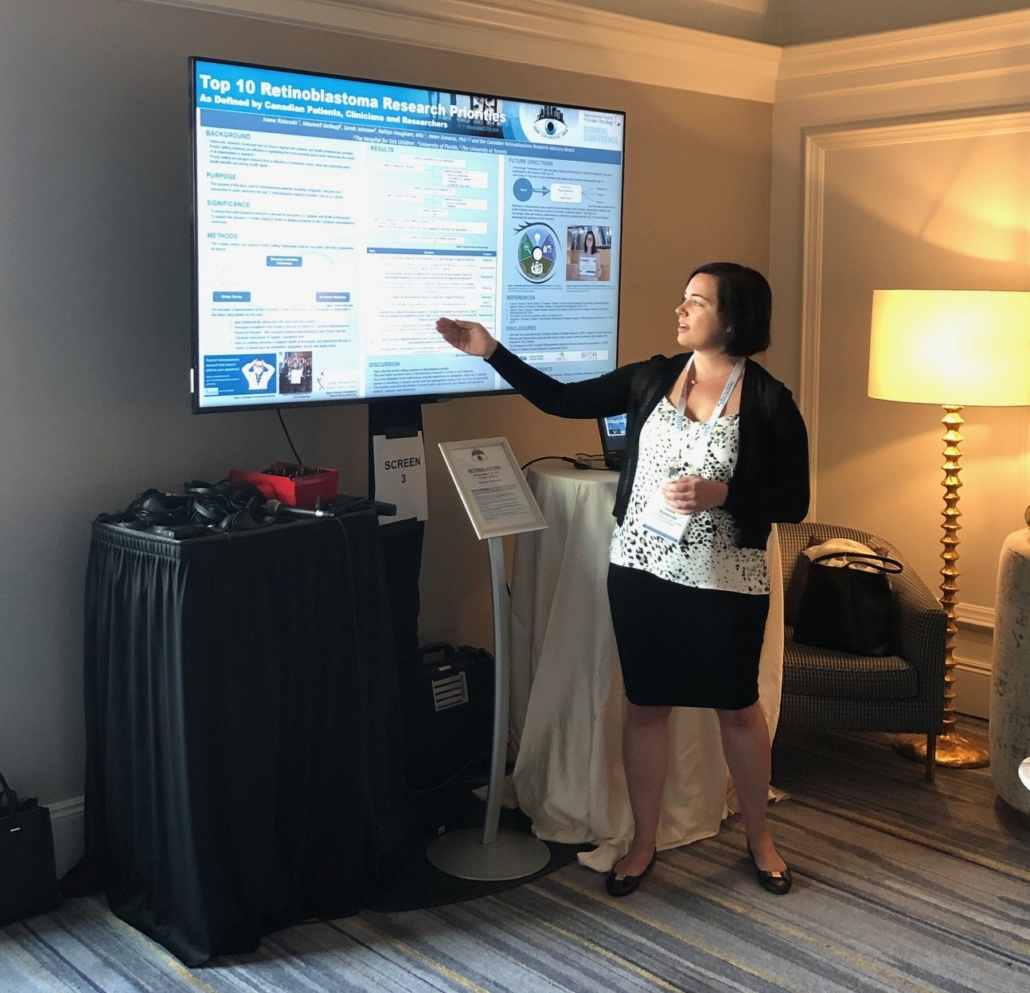 """Ivana Ristevski stands beside her poster, presented on a large digital screen, pointing to an element within it as she presents on the project it describes. The title, """"The Top 10 Retinoblastoma Research Priorities in Canada as Determined by Patients, Clinicians, and Researchers"""", is clearly readable. Other elements are not legible in the photograph."""