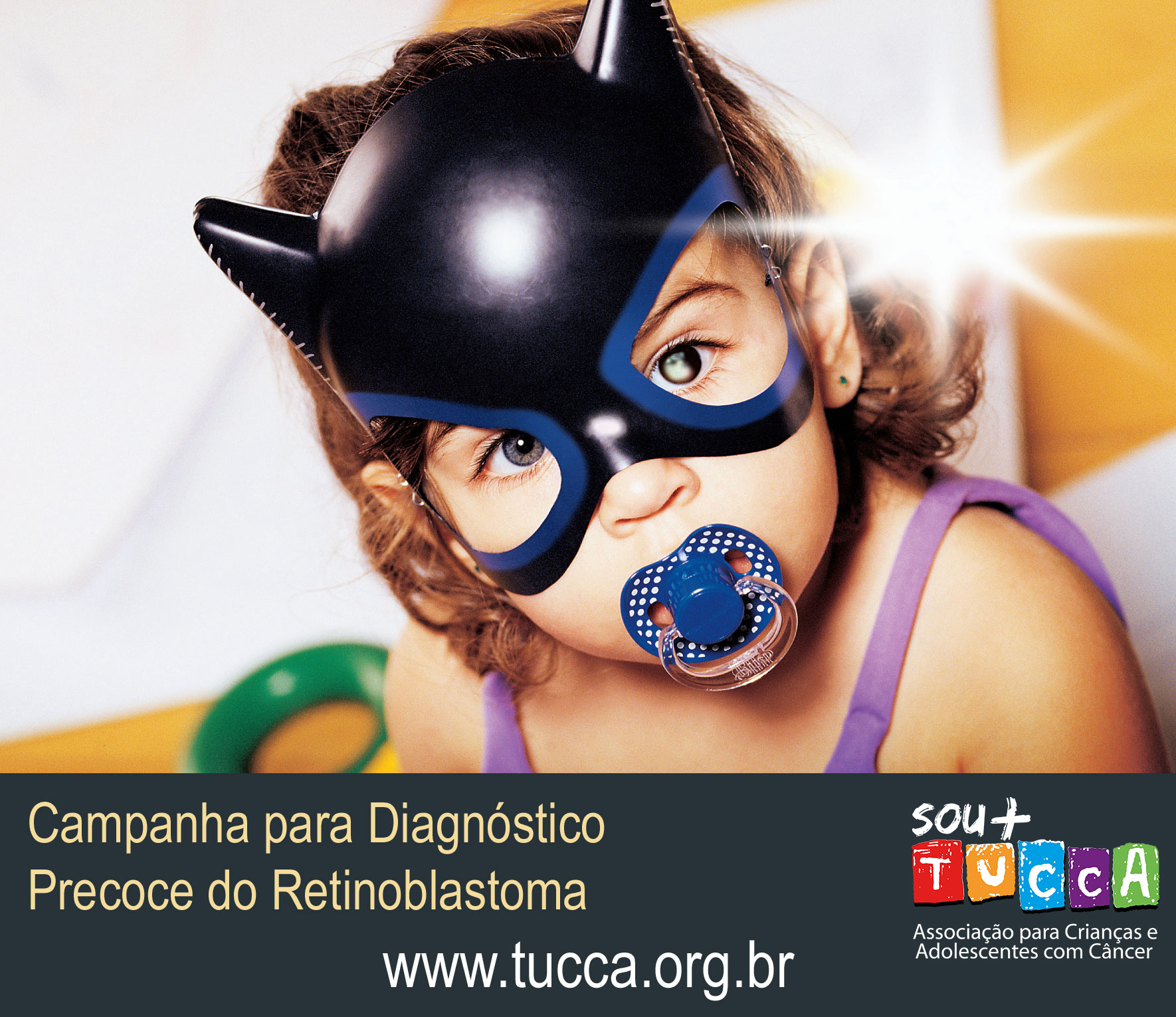"A Portuguese language awareness poster features a large photo of a child, with a text panel below. The child wears a superhero mask with eye cut-outs. A bright white reflection is clearly visible in the left eye. This is emphasized by reflections of light bouncing off the mask, and a hazy white star-flash superimposed onto the image beside the eye. The child's young age is emphasized by the presence of a pacifier in his mouth. Text below reads: ""Campanha para Diagnostico Precoce do Retinoblastoma. www.tucca.org.br SOU + TUCCA Associação para Crianças e Adolescentes com Câncer"""