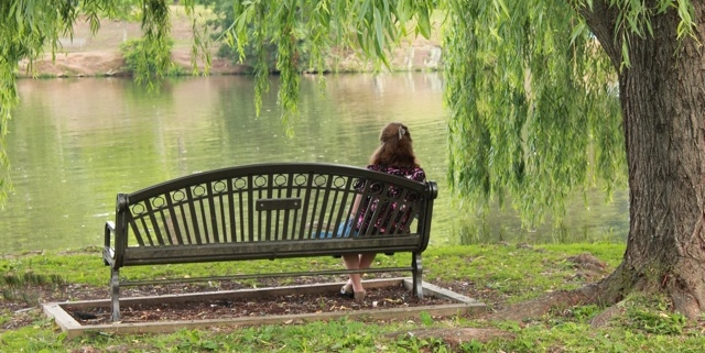 A woman sits alone on a bench under a sprawling weeping willow tree in a park. She is facing away from the camera.