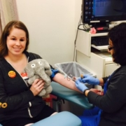 A young lady reclines in a hospital chair, holding a cute grey elephant with big eyes, while a nurse takes a blood sample from her arm.