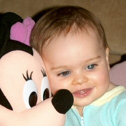 A child hugs Mickey Mouse. A white glow is clearly visible in her left eye.