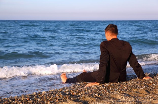 A man wearing a black suit sits alone on a beach, his legs stretched out, heals resting in the surf at the water's edge. The sky is clear and the sea deep blue. The man is facing away from the camera, head turned slightly downwards.