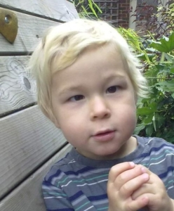 a blond-haired boy looks towards the camera. His left eye looks forward while his right eye turned inward towards his nose.