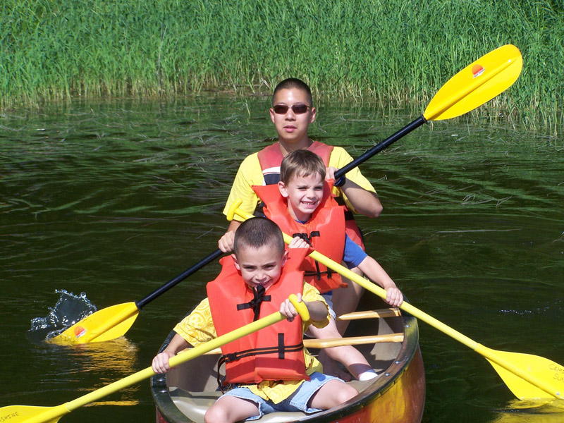 Two children and their camp counsellor are pictured from the front in a kayak. At the back, the counsellor is wearing sunglasses and using a double ended oar, while the smiling boys have smaller, single ended paddles, all with bright yellow blades. All three are wearing orange life jackets, and the camp counsellor and child at the front are also wearing yellow Camp Sunshine t-shirts. The verdant green backdrop is reflected in the water surrounding them.