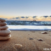 Five smooth pebbles are stacked in decreasing size on a beach, where lively surf rolls into shore. The high sky is clear blue, with a few clouds above the horizon, which is lightly tinged with a pale peachy glow of sunrise or sunset.