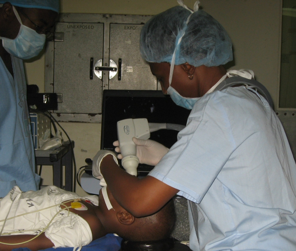 An African doctor looks on as another uses a handheld digital camera to visualise a child's eyes during an exam under anaesthesia.