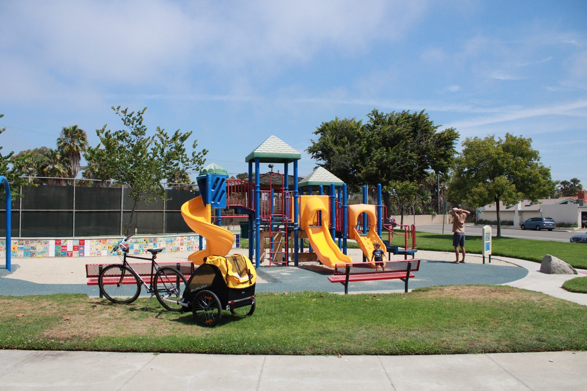 Brightly coloured playground with three slides surrounded by an area of sand, of bouncy recycled tire, a large grassy area and patio.